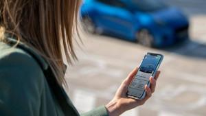 Person mit FordPass Connect App und Ford Puma im Hintergrund